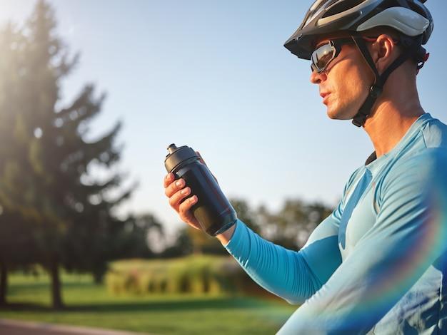L'idratazione conta un ciclista professionista maschio che tiene una bottiglia d'acqua in piedi con la sua bici nel parco acceso