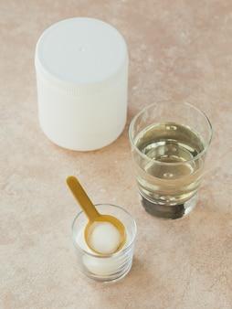 Peptidi di collagene di origine marina idrolizzati in una ciotola di vetro e acqua su un beige chiaro.
