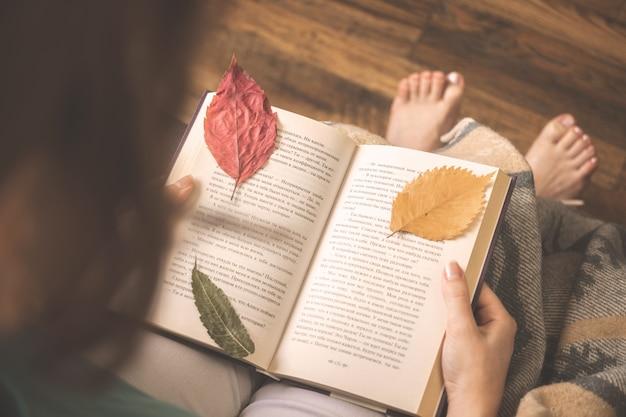 Concetto di hygge con ragazza e libro con foglie d'autunno. foto di sfondo accogliente a casa