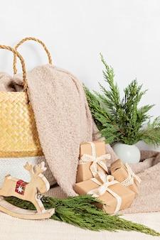 Regali avvolti in carta ecologica hygge con cestino e coperta calda e morbida. decorazioni e regali di natale scandinavo a rifiuti zero