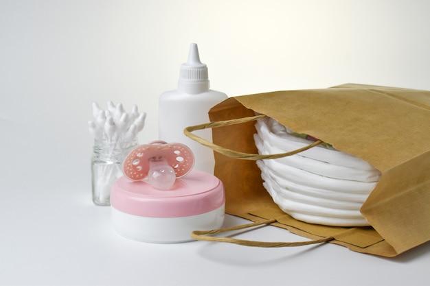 Prodotti per l'igiene e la cura del corpo per il bambino. pannolini e mutandine, crema, ciuccio e borotalco in un sacchetto di carta