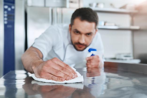 Precauzioni igieniche lavoratore nella cucina del ristorante che pulisce dopo il servizio di messa a fuoco selettiva sul suo