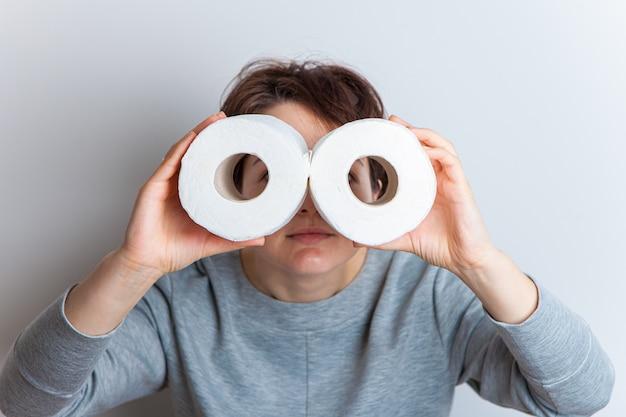 Hype con carta igienica, la donna tiene in mano due rotoli di carta igienica raffiguranti binocoli o bicchieri