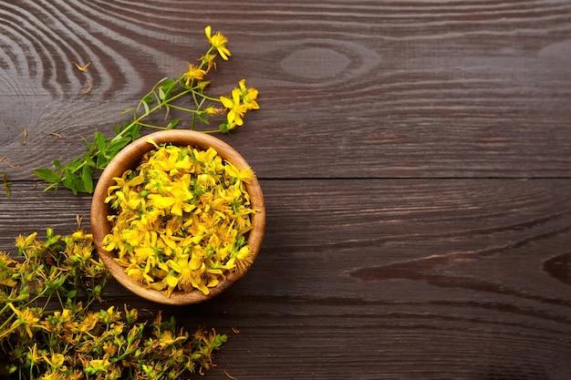 Hypericum perforatum o erba di san giovanni pianta medicinale fiori in ciotola di legno
