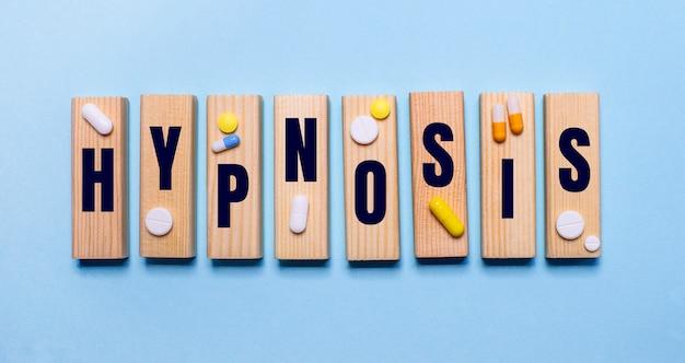 L'ipnosi è scritta su blocchi di legno su un tavolo azzurro vicino alle pillole. concetto medico
