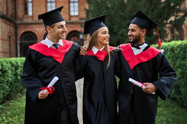 Hyppy sorridente tre laureati che camminano nel campus universitario e festeggiano la laurea.