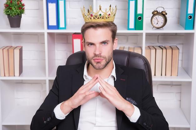 Sono il grande capo qui. grande capo in ufficio. il grande capo indossa una corona sulla testa. direttore o grande capo. uomo d'affari o amministratore delegato sicuro. datore di lavoro di successo. abbigliamento formale e moda da lavoro. segui il tuo capo.