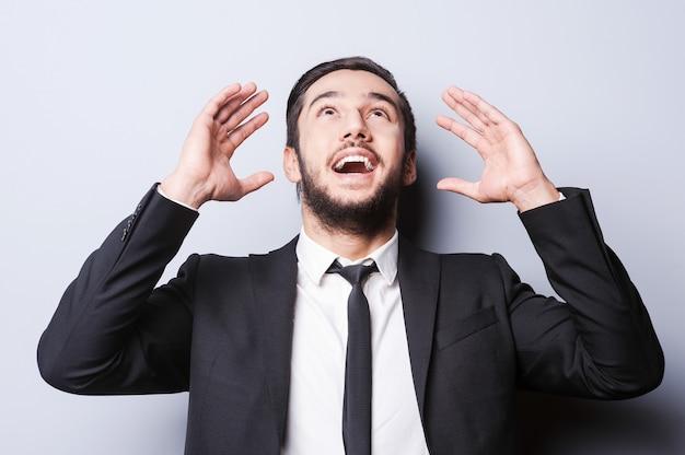 Sono un genio! felice giovane uomo in abiti da cerimonia che gesticola e sorride mentre sta in piedi su uno sfondo grigio