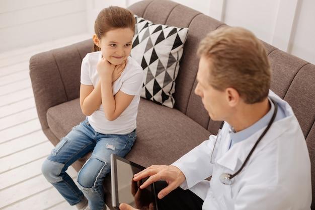 Ho un po 'freddo. dolce bella ragazza che visita un medico e spiega i suoi sintomi mentre entrambi seduti su un divano