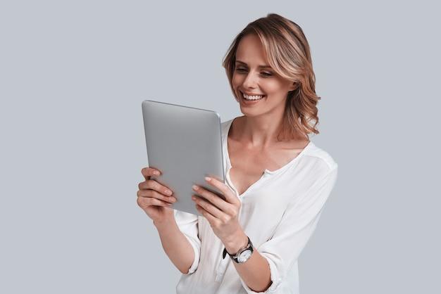 Sono online! bella giovane donna che guarda il tavolo digitale e sorride mentre si trova su uno sfondo grigio gray
