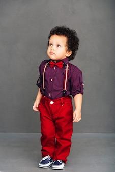 Sono pronto per un appuntamento! piccolo neonato africano che guarda lontano mentre sta in piedi su sfondo grigio
