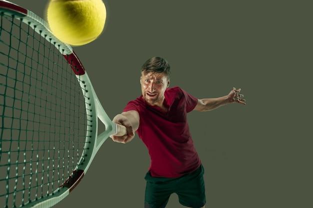Sto salvando questa palla ora. affondo del giocatore, gioco di difesa. l'unico uomo caucasico in forma che gioca a tennis in studio. giocatore isolato su sfondo grigio in piena lunghezza con racchetta e palla. emozioni in faccia