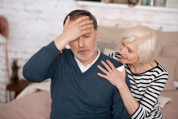 Sono malato. uomo anziano che si sente male e si tocca la fronte mentre sua moglie sta cercando di sostenerlo.