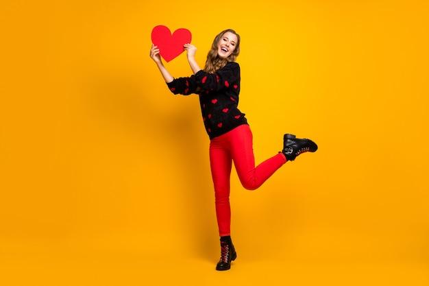 Ti prendo! foto a figura intera di bella signora tenere cuore di carta data creativa invito fidanzato indossare cuori modello maglione rosso pantaloni scarpe