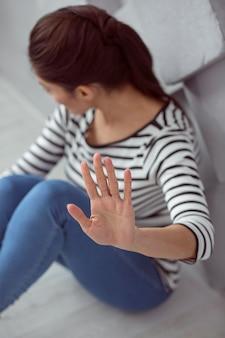 Non voglio niente. giovane donna depressa e triste che si siede sul pavimento e si allontana da te mentre mostra il suo rifiuto