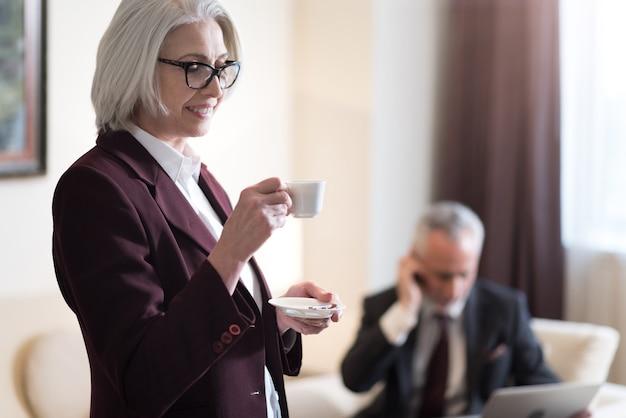 Mi piace la mia pausa caffè. felice imprenditrice invecchiata felice sorridente e bere un caffè in piedi in ufficio e il suo collega che lavora con un computer portatile