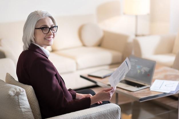 Mi piace il mio lavoro. felice imprenditrice invecchiata felice sorridente e in possesso di documenti mentre era seduto in ufficio davanti al computer portatile ed esprimendo gioia