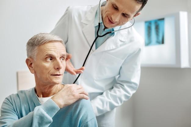Sento dolore qui simpatico uomo invecchiato piacevole che si rivolge al medico e spiega dove sente dolore durante un controllo medico