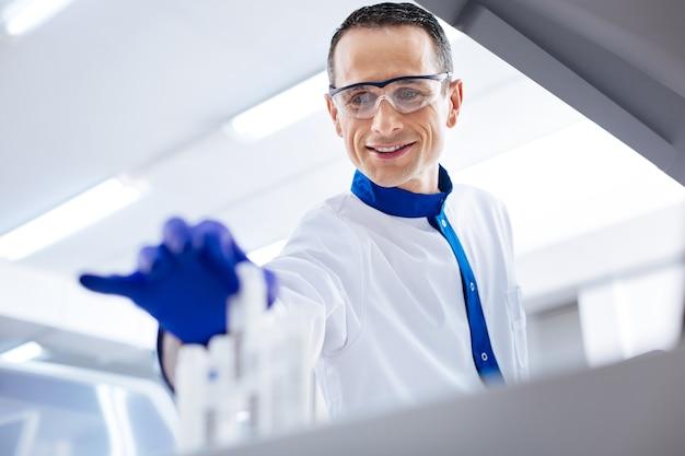 L'ho trovato scienziato maschio felice e allegro che decide sui farmaci mentre indossa occhiali medici e tiene un contenitore