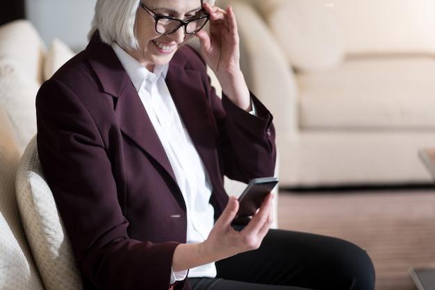 Prendo conoscenza delle moderne tecnologie. piacevole donna di affari invecchiata affascinante tenendo il telefono e gli occhiali mentre era seduto in ufficio e guardando il cellulare
