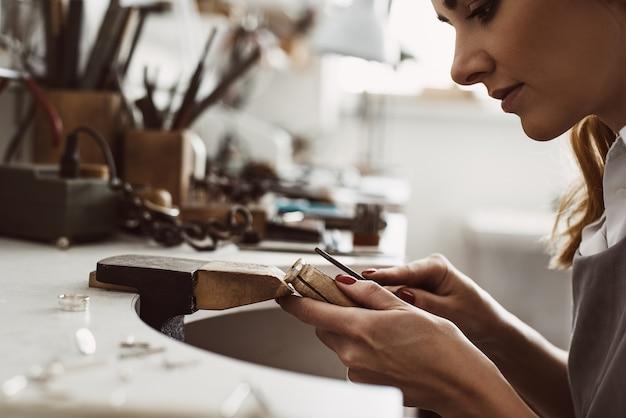 Ho avuto la mia ispirazione vista laterale di un gioielliere eccitato femminile che crea un anello d'argento