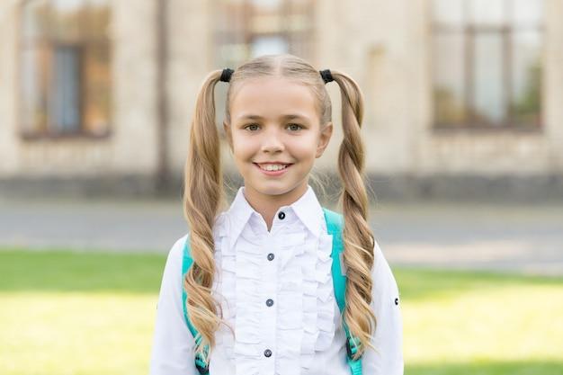 Ho nuove regole. primo giorno di scuola. fondo urbano della scolara felice. piccola studentessa torna a scuola. la piccola studentessa indossa l'uniforme formale. sguardo affascinante di studentessa carina. scuola ed educazione.