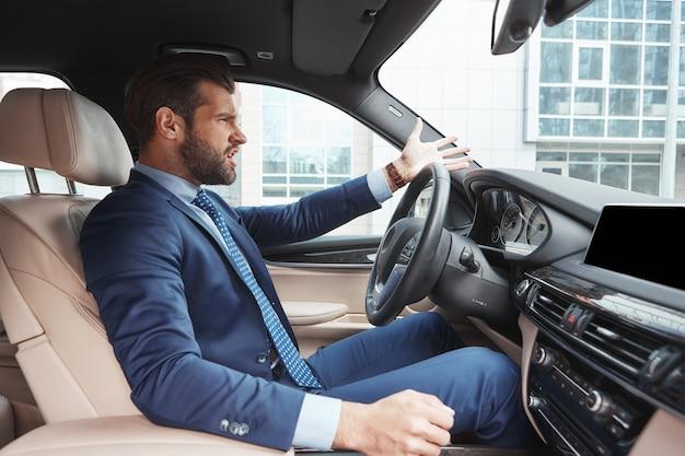 Odio essere in ritardo la vista laterale dell'uomo d'affari barbuto arrabbiato in abbigliamento formale sta gesticolando