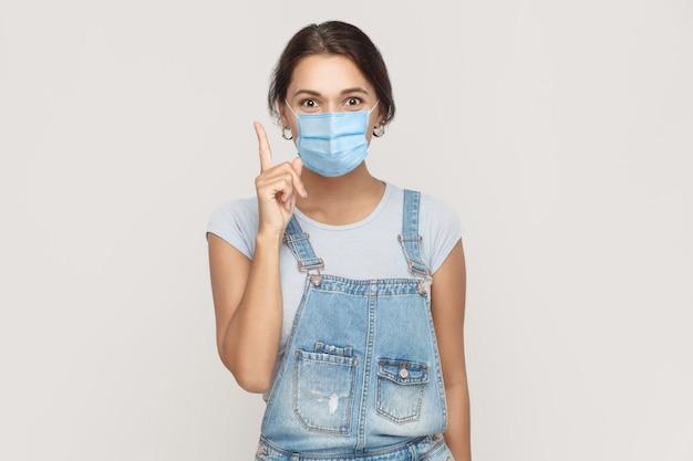 Ho un'idea. ritratto di giovane donna bruna felice con maschera medica chirurgica in tuta di jeans in piedi sorpresa e guardando la telecamera sorridendo. studio al coperto colpo isolato su sfondo grigio.