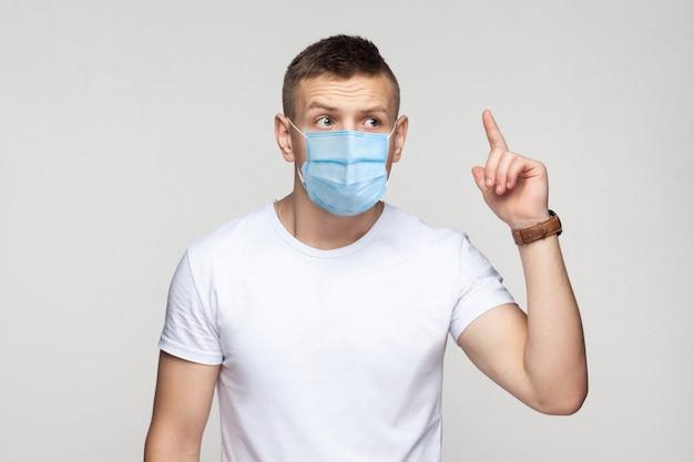 Ho un'idea. ritratto di giovane premuroso in camicia bianca con maschera medica chirurgica in piedi e cerca di ricordare la sua idea. girato in studio al coperto, isolato su sfondo grigio.