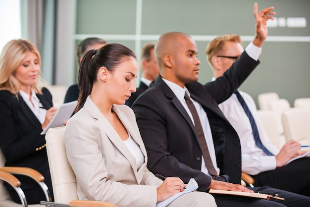 Ho una domanda! gruppo di uomini d'affari in abiti da cerimonia seduti alle sedie nella sala conferenze e scrivere qualcosa sui loro taccuini mentre un bell'uomo africano alza il braccio