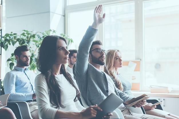 Ho una domanda! gruppo di giovani seduti in conferenza insieme mentre un uomo alza la mano