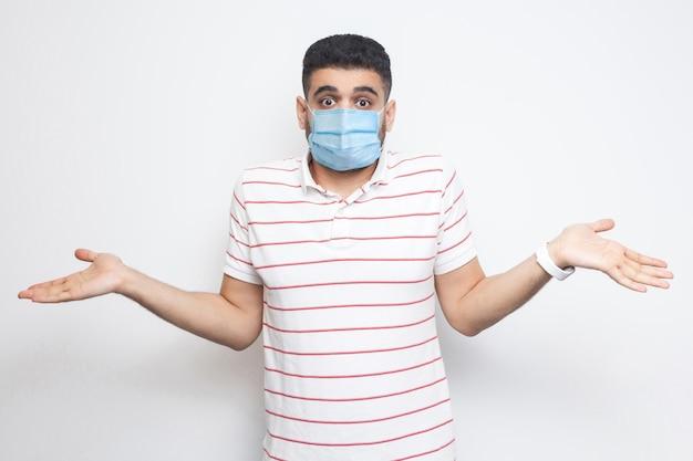 Non lo so. ritratto di giovane confuso con maschera medica chirurgica in maglietta a righe in piedi con le braccia alzate e non sa cosa fare. girato in studio al coperto, isolato su sfondo bianco.