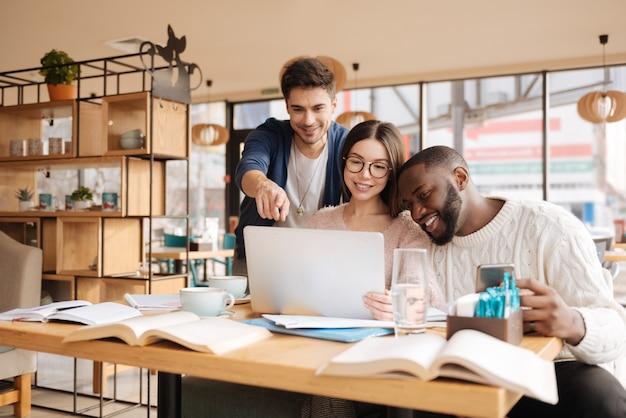 Mi piace. il giovane uomo bello sta indicando lo schermo del laptop mentre era seduto al caffè e studiava con i suoi due compagni.