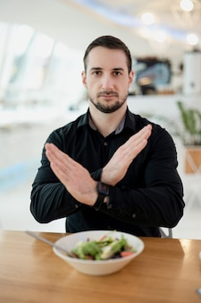 Non mi piace questo piatto! attraente uomo serio incrociando le mani in disaccordo gesto. è stanco di mangiare solo insalate e cibi sani. concetto di cibo e servizio pessimo. ristorante sullo sfondo.