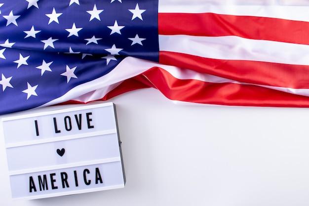 Adoro il testo america in una scatola luminosa con una bandiera americana su sfondo bianco. memorial day, giorno dell'indipendenza, festa dei veterani.