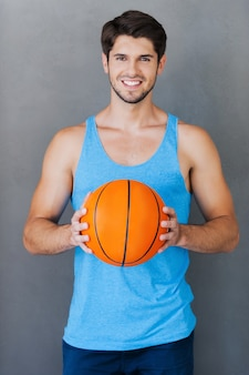 Amo il basket! sorridente giovane uomo muscoloso che tiene la palla da basket mentre in piedi su sfondi grigi