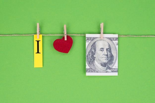Amo il concetto di franklin. vista ravvicinata foto di denaro usd americano e piccolo cuore rosso attaccato sulla corda isolato su sfondo verde brillante