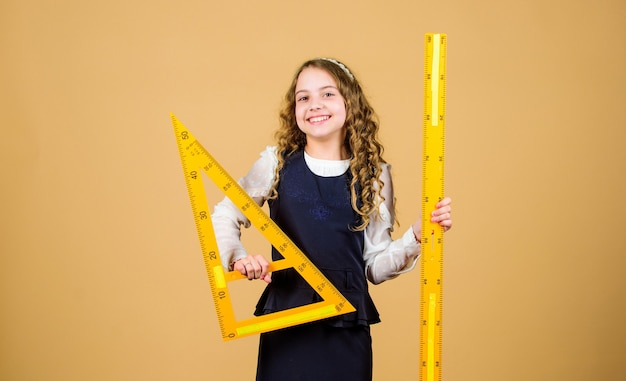 Amo la matematica. istruzione e concetto di scuola. concetto intelligente e intelligente. dimensionamento e misurazione. allievo ragazza carina con grande righello. geometria di studio dello studente della scuola. righello della tenuta dell'uniforme scolastica per bambini.