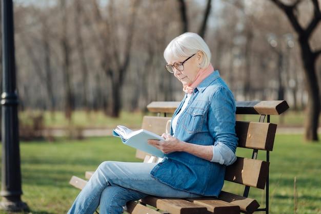 Amo leggere. donna bionda concentrata che legge un libro mentre era seduto sulla panchina