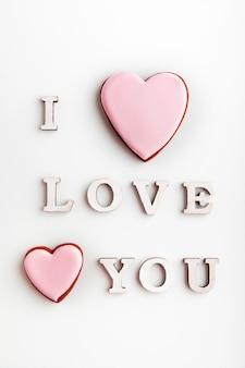 Ti amo scritta su sfondo bianco accanto a biscotti di panpepato con glassa rosa
