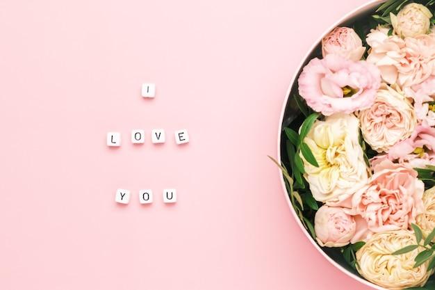 Ti amo scritte sui quadrati di legno con lettere sullo sfondo rosa e grande scatola rotonda
