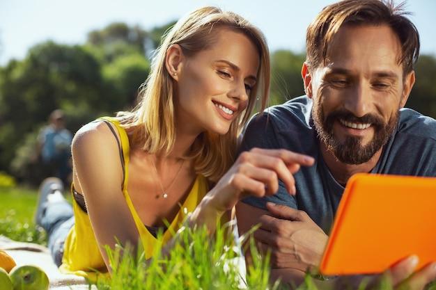 Ti amo. donna abbastanza allegra guardando il tablet mentre ci si rilassa all'aperto con il marito