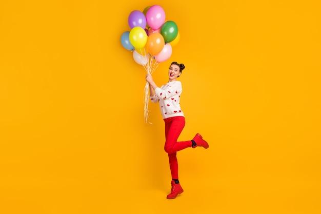 Io volerò! la foto di profilo a figura intera della signora porta molti palloncini colorati a sorpresa con un maglione con motivo a cuori