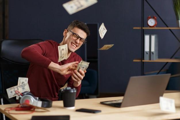 Sono ricco. ritratto di un giovane libero professionista o uomo d'affari in un ministero degli interni. lancia contanti. affare riuscito. guadagno on line. vinci i soldi.