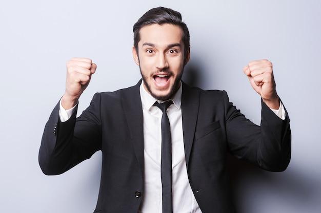 Sono arrivato in cima! felice giovane uomo in abiti da cerimonia che gesticola e sorride mentre sta in piedi su uno sfondo grigio