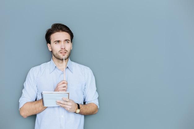 Ho bisogno di ispirazione. bel bell'uomo premuroso che tiene una matita e se la mette al mento durante la ricerca di nuove idee