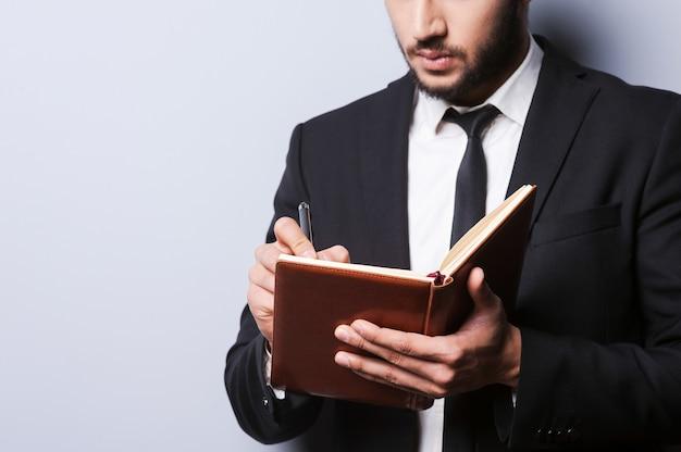 Ho bisogno di nuove idee. primo piano di un giovane in abiti da cerimonia che tiene un blocco note e ci scrive con una penna mentre si trova in piedi su uno sfondo grigio