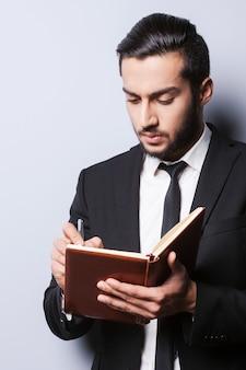Ho bisogno di nuove idee. giovane concentrato in abiti da cerimonia che tiene in mano un blocco note e ci scrive con una penna mentre si trova in piedi su uno sfondo grigio