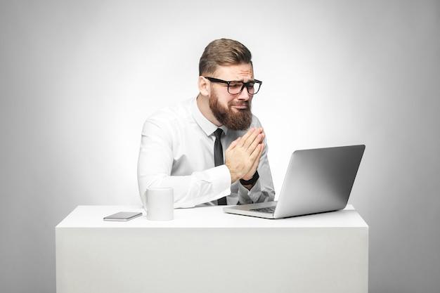 Ho bisogno del tuo aiuto! ritratto di speranzoso giovane manager barbuto in camicia bianca e cravatta nera sono seduti in ufficio e parlano con un amico pensato skype e sono contento di averlo aiutato nel compito di lavoro. isolato