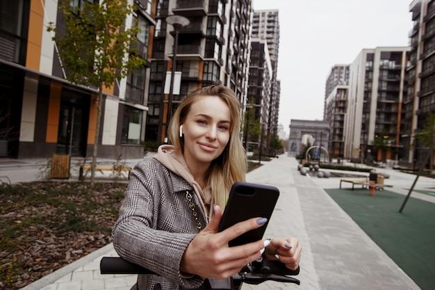 Mi piace molto questa applicazione per il noleggio di scooter! attraente donna in cappotto si appoggia al volante di uno scooter, tiene uno smartphone in mano e guarda la telecamera.